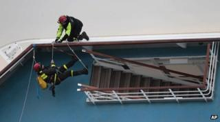 Rescue workers attempt to board the stricken Costa Concordia