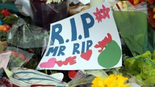 Pupils lay flowers in tribute to teacher killed in coach crash.