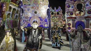 Dancers with glittery masks take part in the first night of the Rio carnival.