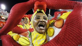 A woman dressed in yellow carrying a huge mouth takes part in the opening night of Rio carnival.