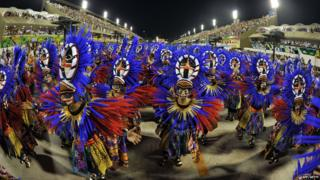 A dance group dressed in purple and orange take part in the opening night of the Rio carnival.