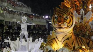 A man dances on a platform next to a tiger float on the opening night of the Rio carnival.