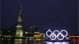 Olympic rings float past the Shard skyscraper with Waterloo Bridge in the background.