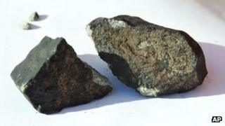 The meteorite which fell through the roof of a shed in Oslo. It is broken in two pieces and is grey.