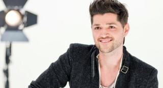 Danny O'Donoghue in a publicity photograph for BBC The Voice. He sits in a studio smiling, wearing a smart, trendy black jacket.