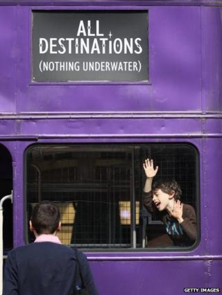 Two visitors play on one of the buses at the Harry Potter studio tour.