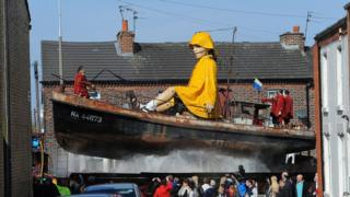 Little Girl Giant rides through the streets of Liverpool on a boat.