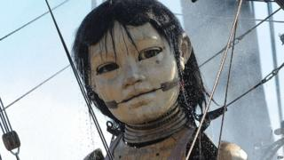 "A giant puppet, part of a street theatre production entitled ""Sea Odyssey"", has a shower in the morning in Stanley Park."