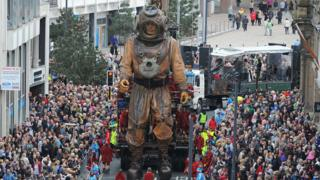 A huge marionette sea diver character walks through the street, surrounded by a crowd of people.