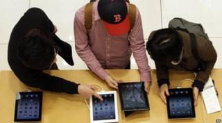three people looking at tablet computers