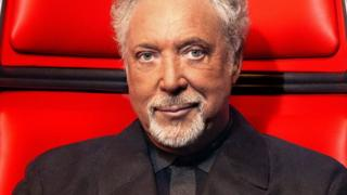 Sir Tom Jones sits in a big red chair on the set of The Voice UK.