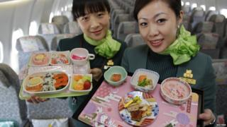 Two flight attendants holding the on board food