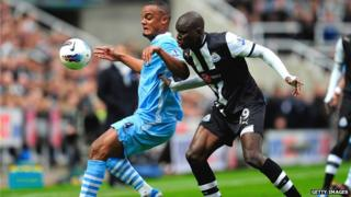 Vincent Kompany and Demba Ba fight for the ball