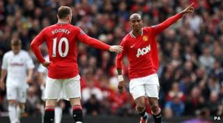 Ashley Young waving to Wayne Rooney