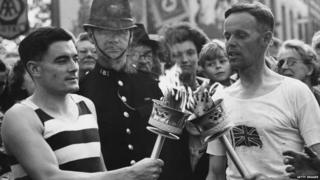 Veteran runner H J Bignall (right) hands over the Olympic torch to Fred Prevett at Redhill, Surrey, during the flame's journey from Dover to Wembley Stadium, London, for the opening of the 1948 London Olympics.