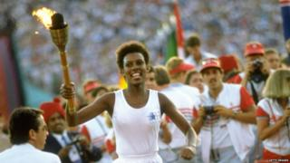 Gina Hemphill runs through the stadium with the Olympic Torch before the 1984 Olympic Games at the Coliseum Stadium in Los Angeles, USA