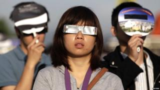 People observe an annular eclipse at Taipei Astronomical Museum.