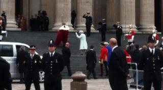 Queen waving on steps of cathedral