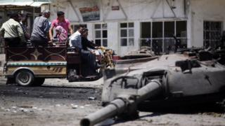 Syrians look at a destroyed military tank