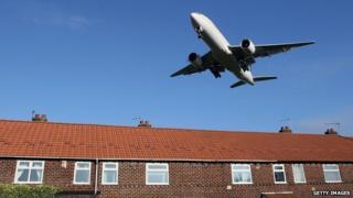 Aeroplane flying low over houses