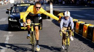Overall leader in the yellow jersey, British Bradley Wiggins parades with his son at the end of the Tour de France. The cycling race started in Rambouillet and finished in the famous Paris-Champs-Elysees Avenue, on July 22, 2012.