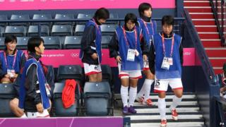 North Korean womens football team walking from seats in football stand