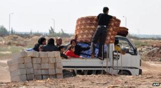 Syrian civilians flee the northern city of Aleppo during a lull in fighting between opposition forces and army troops.