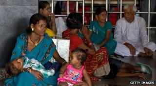 A family waits in a train station following a power cut in India