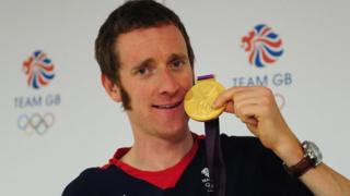 Cyclist Bradley Wiggins holding his London 2012 gold medal