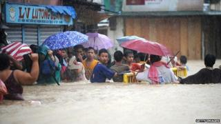 Residents wade through a flooded street under heavy rains
