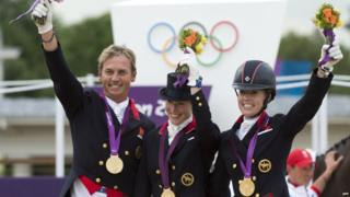 Riders Carl Hester, Laura Bechtolsheimer and Charlotte Dujardin getting gold medals