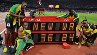 Jamaican 4x100m relay team pose by clock showing their new world record
