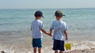 Twins hold hands on the edge of the sea.