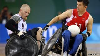 Two wheelchair rugby players collide