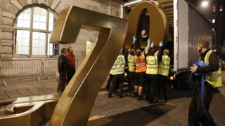 Workmen lift the iconic numbers 007 down from a lorry in preparation for the Royal premiere of Skyfall.