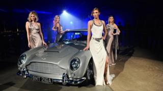 Models pose with the Aston Martin car from the film.