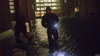 Security guard walks through flood water in the financial district in New York.