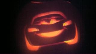 A pumpkin with a carving of Lightning McQueen from the movie Cars.