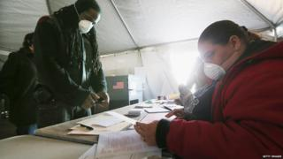 Rockaway resident Jesse James (left) prepares to vote in a makeshift tent set up in the Queens borough of New York City
