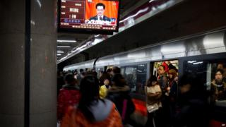 Subway commuters beneath a subway station television showing a live broadcast of Chinese President Hu Jintao's remarks during the opening session of the Communist Party congress in Beijing, 8 November 2012