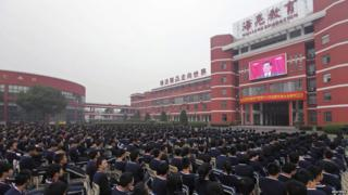 High school students in Zhuji watch a screen showing the Chinese president delivering a keynote report during the opening ceremony.