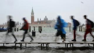"Tourists walk on footbridges during a ""acqua alta"" on November 11, 2012 in Venice. Rain and wind hit the north of Italy on Sunday and the flooding reached 150 centimetres in Venice."