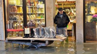 "A shoes seller displays wellies outside his shop in a flooded street during a ""acqua alta"" on November 11, 2012 in Venice."