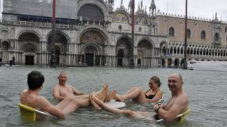 People sit at the table of a bar in a flooded St. Mark's Square in Venice, Italy, Sunday, Nov. 11, 2012.