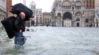 "A man carries luggage on a flooded St Mark's square during a ""acqua alta"" on November 11, 2012 in Venice."