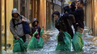 People wade through he flooded streets in Venice after flooding.