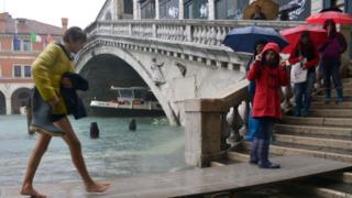 "Tourists walk on footbridges near the Rialto bridge during a ""acqua alta"" on November 11, 2012 in Venice. Rain and wind hit the north of Italy on Sunday and the flooding reached 150 centimetres in Venice."