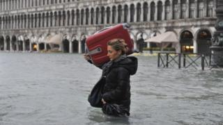 A tourist crosses flooded St. Mark's Square in Venice, Italy, Sunday.