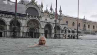 A man enjoys swimming in flooded St. Mark's Square in Venice, Italy.
