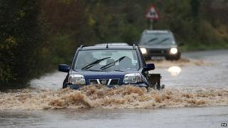 Car drives through flooded road in Worcestershire